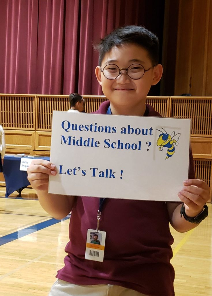 Middle school boy asking if anyone has questions about middle school