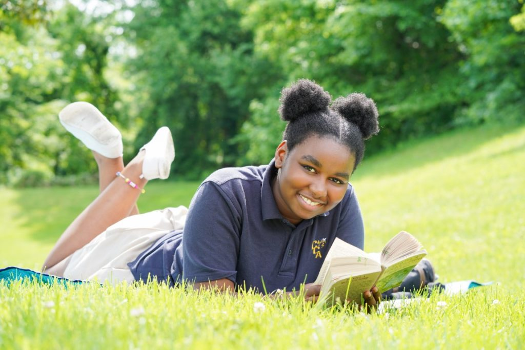 Student studying on lawn