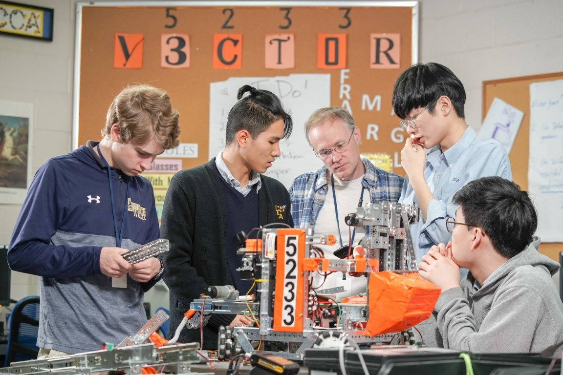 Team Vector working on robot with faculty advisor